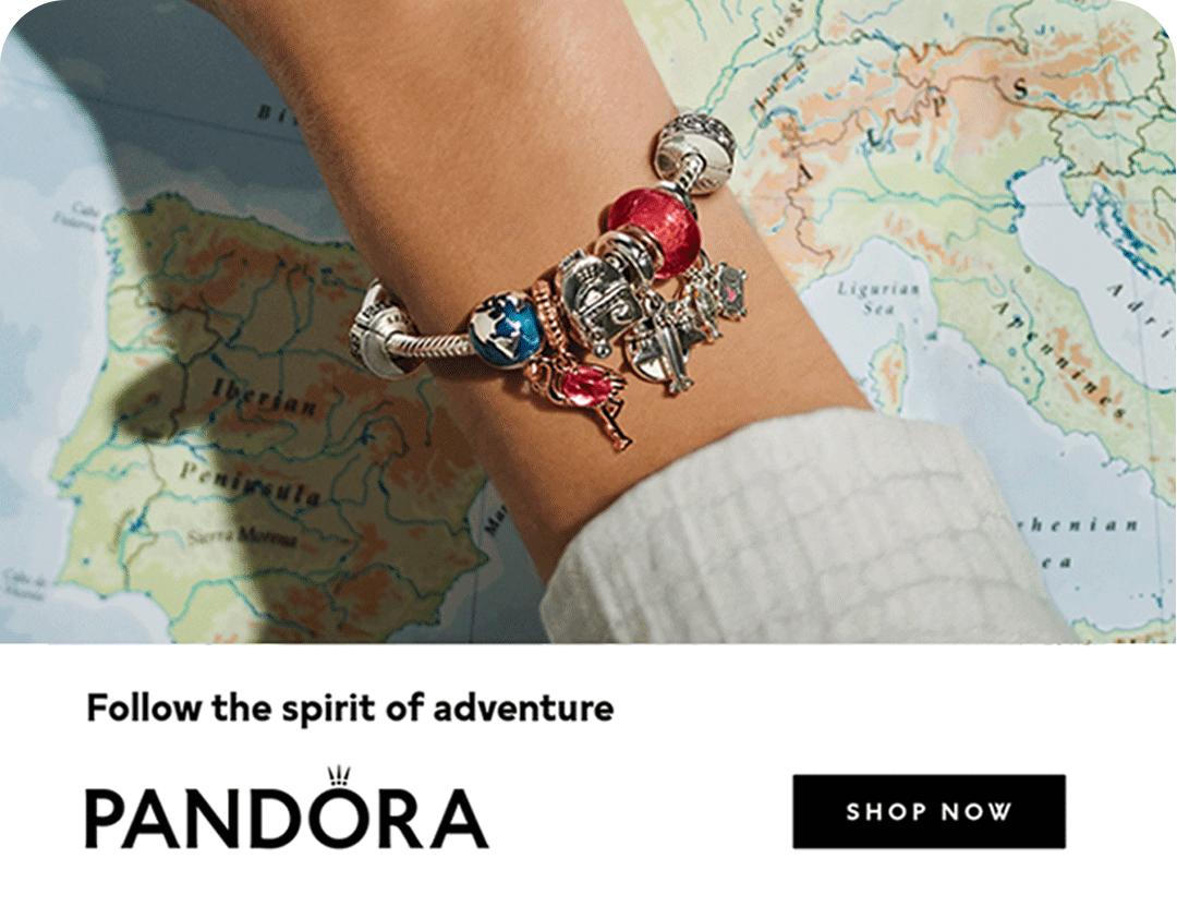 A close up of a Pandora bracelet full of charm on a wrist